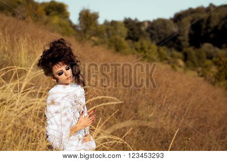 Beautiful, attractive, nice, pretty, nice girl in the sunny, meadow, yellow field with many flowers, wheat, ears, white dress, professional hairstyle, make up, smokey eyes. Beautiful, romantic girl in golden field