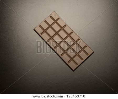 Very sweet delicious chocolate squares on a dark surface.