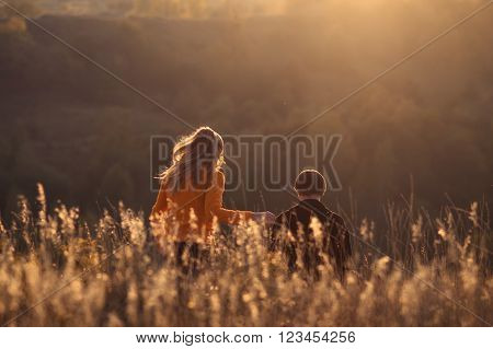 In search of adventures. Enamored couple. Boy and long-haired beautiful blonde girl plays, walks on hill with beautiful view, sunset in sunny meadow field. Man and woman have happy, funny time, date. Love.