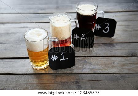 Glass mugs with different sorts of craft beer and numbering on wooden table