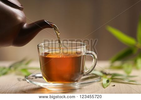Teapot pouring tea in cup