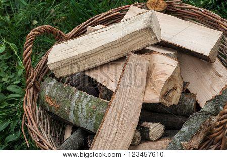 Basket of cut logs fire wood on green grass environmental concept