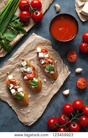 Bruschetta traditional Italian antipasti snack food with roasted baguette tomatoes, feta, basil and garlic. Top view
