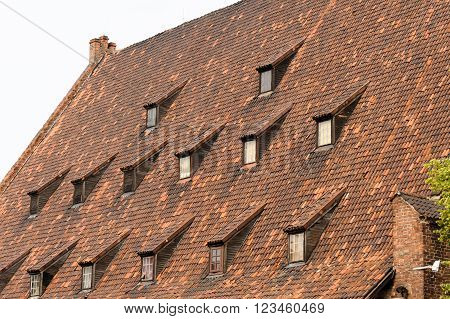 Closeup of the steep tiled roof of the mid-14th century Grand Mill on the Radunia canal in Gdansk