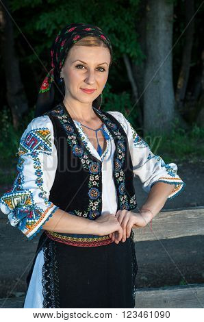 Portrait Of Young Beautiful Woman Posing Outside In Romanian Traditional Costume
