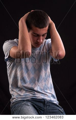 Upset Teenager With Head In Hands Wincing From Stress, Anguish Or Depression