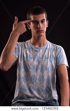 Depressed Teenager Holding Hand Like A Gun To His Head