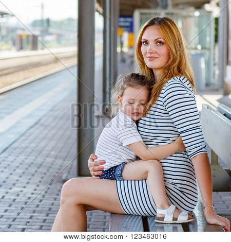 Beautiful family of two: little girl and mother. Hugging and waiting for train on station. People, travel, family, lifestyle concept