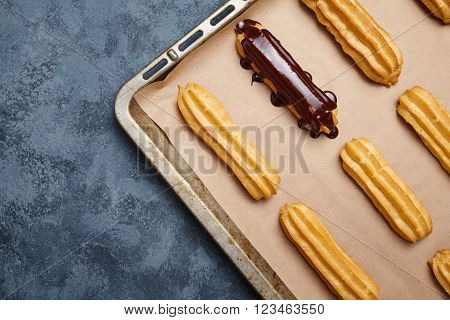 Eclairs or profiterole with chocolate preparing on baking sheet background. Traditional homemade French cuisine dessert. Empty space for design text template. Top view.