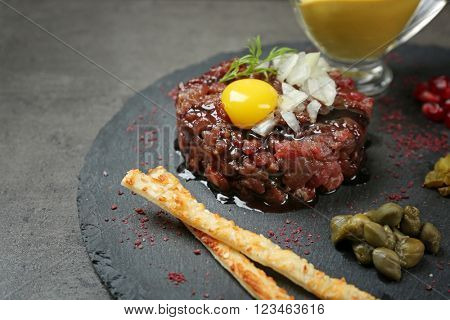 Delicious beef tartare with ingredients on dark background