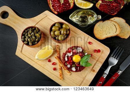 Beef tartare served on a wooden board, close up