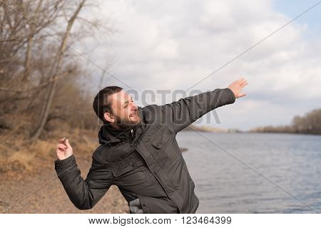 Man with a beard dropping a stone into the river