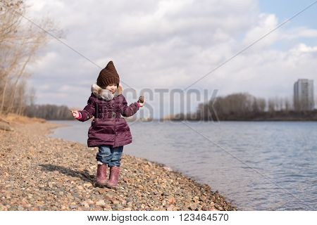 Girl holding a stone on the riverbank