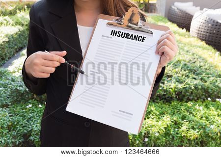 Women in suit showing insurance policy and pointing with a pencil.