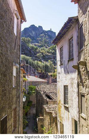background view street, going down the hill and the view of the monastery of the Knights Templar in the village of Monsanto, Portugal