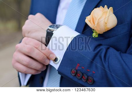 masculine hands hold a cuff-link suit suit wedding fiance