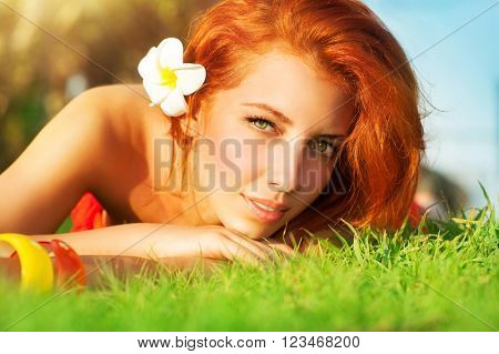 Portrait of cute calm girl lying down on fresh green grass with frangipani flower in red hair, enjoying day spa on the beach resort, young female tanning, summer leisure