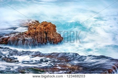 Beautiful rock in the sea, turquoise water flows over cliff at stormy weather day, slow motion scene, beauty of mother nature