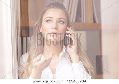 Portrait of beautiful serious business woman speaking on the phone and looking through the window, explaining something to business partner