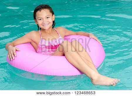 A smiling young girl enjoys the outdoors by floating in a swimming pool.