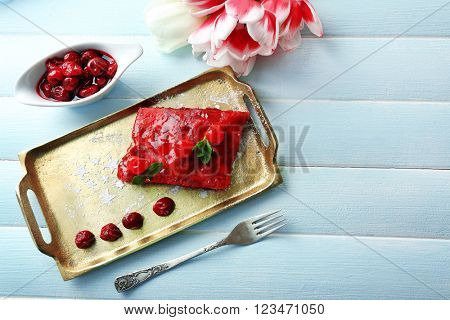 Cherry strudel with mint on wooden table