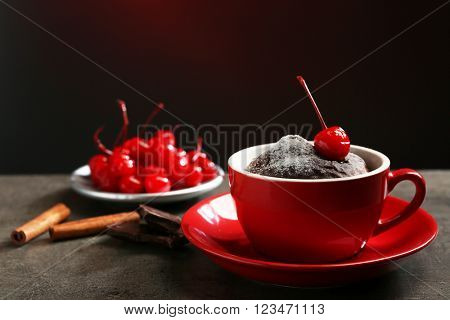 Chocolate cake in a red mug  with a cherry on top, close up
