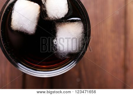 Cocktail with ice blocks  on wooden background, top view