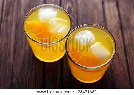 Glasses of orange juice with ice blocks and fruit slice on wooden background