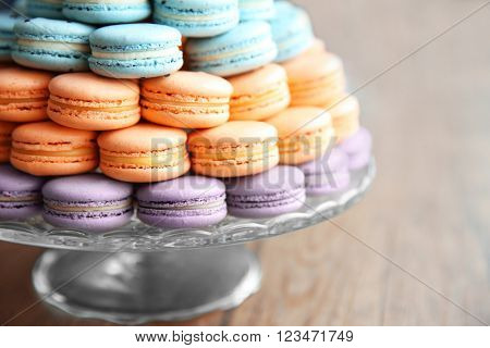Many varicolored tasty macaroons on a dish, close up