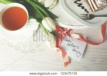 Happy mother day greeting with tulips, cup of tea and delicious cake on wooden table, top view