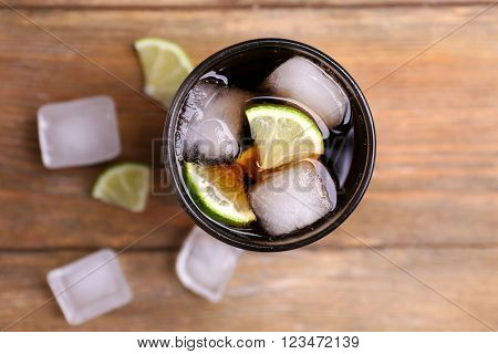Cocktail with lime slices and ice blocks on wooden table, top view