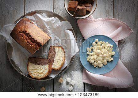 Composition of tasty cake with chocolate morsels and sugar on grey wooden table background, top view