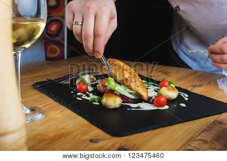 Professional chef decorate plate with meat greens. Man prepares delicious meals in kitchen. Chunks of roasted meat on  black plate with greens, cherry tomatoes and sauce. Close-up. Tweezers in  hand