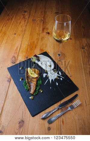 food concept. roasted fish fillet decorated with greens, a slice of lemon, capers. fish and sauce on a black plate. Glass of wine and cutlery.