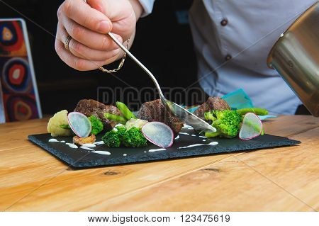 Professional chef decorate plate with meat greens. Man prepares delicious meals in kitchen. Chunks of roasted meat on  black plate with greens, radish, broccoli, asparagus and sauce. Close-up. cook pours sauce meal. In the hands of a spoon.