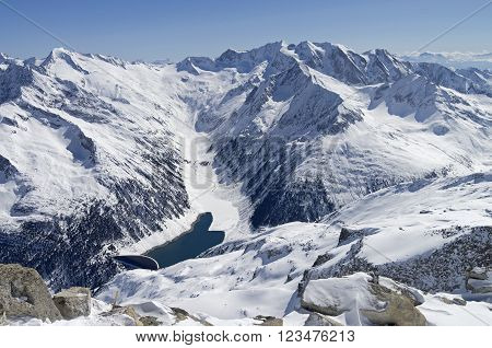 The dam and the artificial lake in a mountain gorge. View from the top of the Hintertux glacier in the Austrian Alps. Height - 3250 meters above sea level. Such small reservoirs used to supply hydroelectric power stations in ithe surrounding valleys