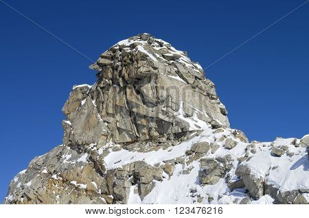 A rock in the shape of the head of a human or a fairy creature. The top of the Hintertux glacier in the Austrian Alps. Height - 3250 meters above sea level.