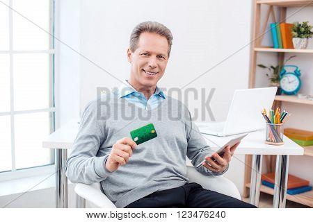 Stylish adult businessman while working day in office. Businessman using tablet computer, showing credit card, looking at camera and smiling. Office interior with bookcase and big window