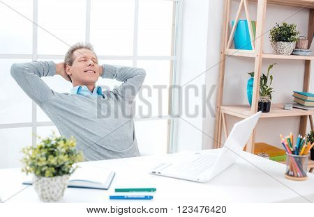 Stylish adult businessman while working day in office. Businessman with laptop, relaxing and smiling. Office interior with bookcase and big window