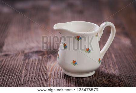 White ceramic teapot, creamer and sugar bowl on dark wooden background