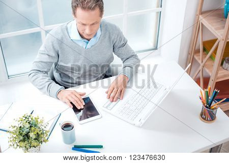 Top view photo of stylish adult businessman while working day in office. Businessman with laptop and tablet computer. Office interior with bookcase and big window