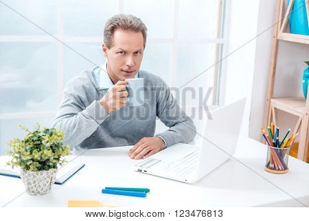 Stylish adult businessman while working day in office. Businessman with laptop, drinking coffee, looking at camera. Office interior with bookcase and big window