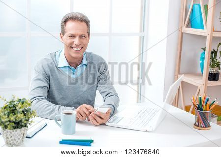Stylish adult businessman while working day in office. Businessman with laptop, using mobile phone, looking at camera and smiling. Office interior with bookcase and big window