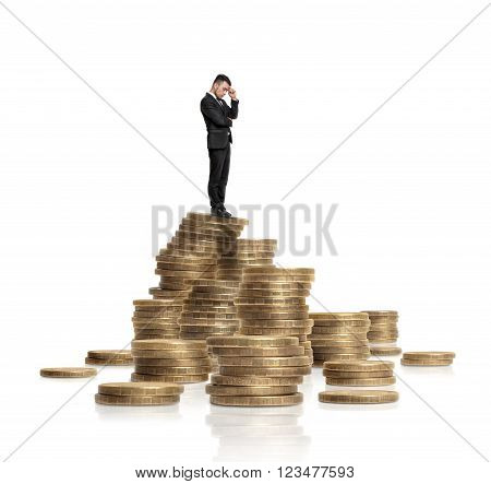 A businessman in a black suit touches his forehead with his hand standing on a heap of glittering golden coins isolated on a white background