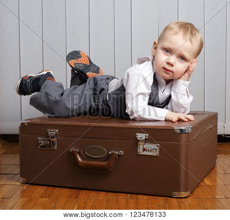 photo of little funny boy in suitcase