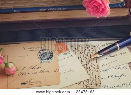 old golden quill pen and antique letters on table with books and roses, retro toned