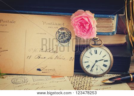 antique pocket  clock with postcard  on vintage  books and letters background, retro toned