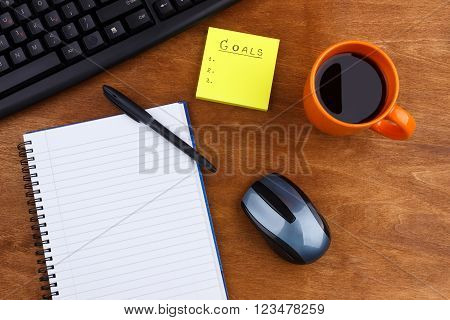 Overhead of office table with computer keyboard, mouse, notepad, coffee mug and pen