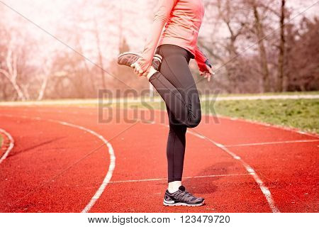 Woman stretching on a running track. Woman running concept. Runner jogging training workout
