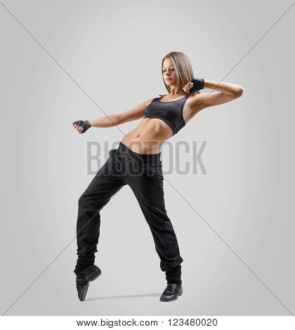 Girl dancer standing sideways and leaning back with lifted up left hand bent at the elbow. Right leg raised on tiptoes. Dance moves.